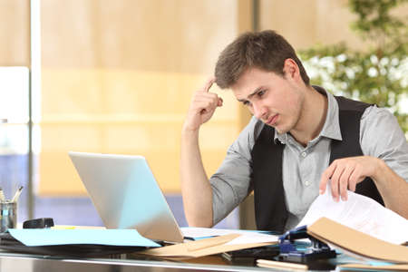 slacker: Incompetent businessman thinking how to do his job online with messy desk at office
