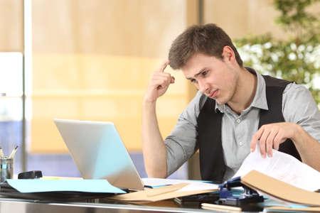 Incompetent zakenman denken hoe hij zijn werk online te doen met slordig bureau op kantoor