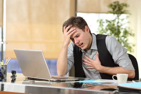 Unternehmer, die einen Angriff Angst mit den Händen in der Brust und Kopf leiden in einem Schreibtisch im Büro sitzen