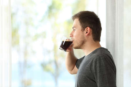 Side view of a man drinking coffee looking through the window of home or hotel