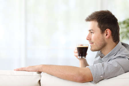 Profile portrait of a handsome man enjoying a cup of coffee relaxing sitting on a couch at home