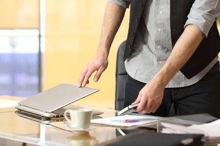職場を去ると、オフィスでノート パソコンを閉じる実業家の手のクローズ アップ