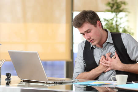 Businessman suffering a heart attack with his hands grabbing the chest sitting in a desktop at office Banco de Imagens