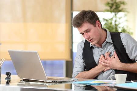 Homme d'affaires souffrant d'une crise cardiaque avec ses mains saisissant le coffre assis dans un bureau au bureau Banque d'images - 65029241