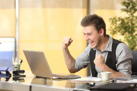 사무실에서 바탕 화면에서 노트북과 라인에서 작업하는 흥분된 성공적인 사업가