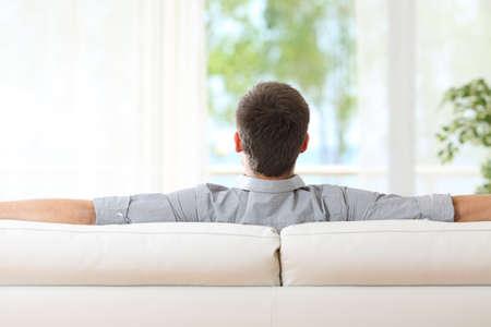 Achteraanzicht van een man ontspannen zitten op een bank thuis en kijkt buitenshuis door het raam thuis