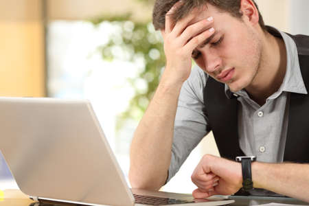 Besorgt Geschäftsmann die Zeit läuft die Uhr im Büro beobachten