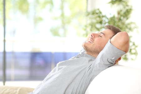 Vista lateral de un hombre feliz atractivo de descanso y la respiración se sienta en un sofá en casa con una ventana con un fondo verde al aire libre