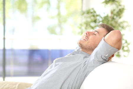 Side view of a happy attractive man resting and breathing sitting on a couch at home with a window with a green background outdoors