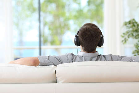 Back view of a man relaxing and listening music with headphones sitting on a couch and looking through the window at home