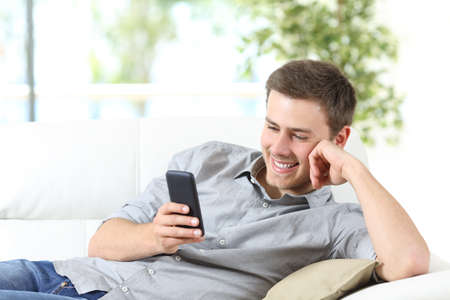 Happy man using a smartphone sitting on a couch at home with a window in the background Фото со стока