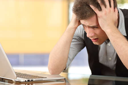 사무실 실내에서 책상에 앉아 머리에 손으로 노트북을보고 걱정 된 기업의 근접 촬영
