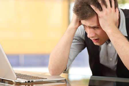 Przeznaczone do walki radioelektronicznej z zmartwiony przedsiębiorca oglądanie komputera przenośnego z rąk na głowie siedzi w biurko w biurze kryty