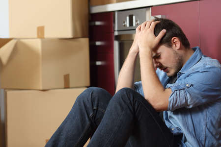 Sad evicted man worried relocating house sitting on the floor in the kitchen Imagens