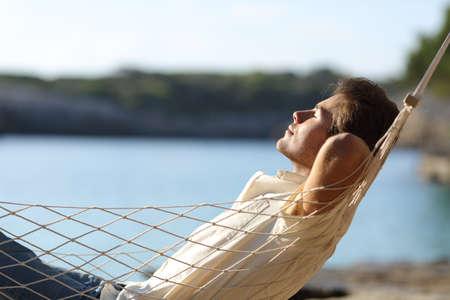 ser humano: Vista lateral de un hombre feliz ocasional que se relaja en una hamaca en la playa en días festivos