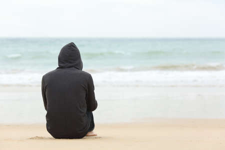 Rear view portrait of one teenager boy thinking alone and watching the sea sitting on the sand of the beach with the horizon in the background