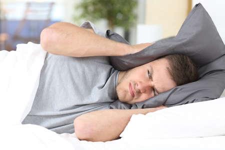 Jeden muž se snaží spát pokrývající uši, aby se zabránilo hluku soused doma nebo v hotelu Reklamní fotografie - 65029318