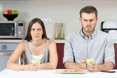 envious: Front view of an angry couple looking each other sideways after argument in the kitchen during breakfast at home