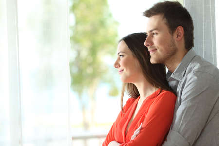Side view portrait of a happy marriage standing hugging and looking outdoors through a window at home or hotel room with a green background
