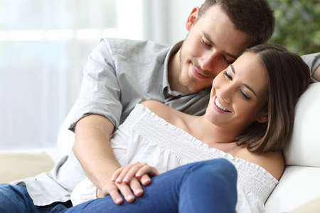 homey: Affectionate couple holding hands sitting on a sofa at home with a homey background. Love concept Stock Photo