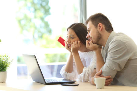 Frustrated buyers trying to pay online with credit card and a laptop at home