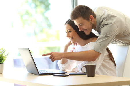 Vue de côté d'un couple heureux recherche d'informations en ligne dans un ordinateur portable sur une table à la maison ou chambre d'hôtel avec une fenêtre en arrière-plan