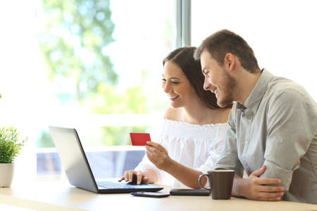 Couple of buyers buying on line with credit card and a laptop at home or hotel Stock Photo