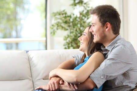 Side view of a happy couple hugging sitting on a couch and looking outdoors through the window at home Stock Photo
