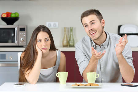 annoyed: Bored wife hearing her husband talking during breakfast in the kitchen at home