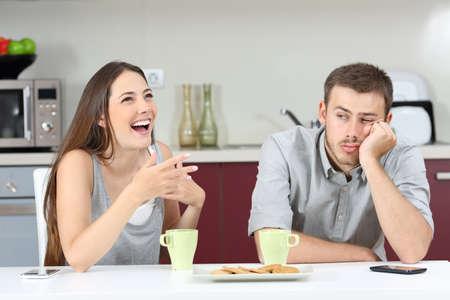 Marido aburrido de oír hablar a su esposa durante el desayuno en la cocina en el hogar Foto de archivo - 65815504