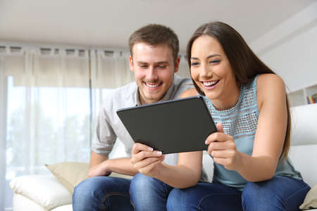Couple enjoying media content in a tablet sitting on a couch in the living room in a house interior