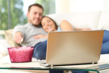 Gelukkig paar dat op TV op de lijn in een laptop en het eten van popcorn liggend op een comfortabele sofa thuis