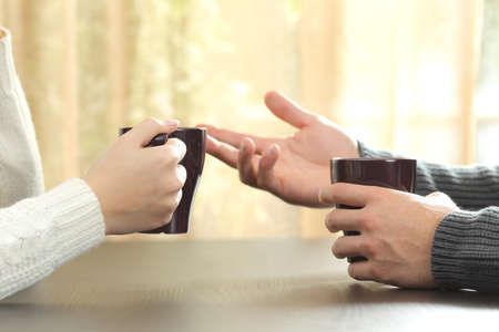 Back light profile of hands of 2 friends or couple talking holding coffee cups sitting in a table at home with a window in the background Stockfoto