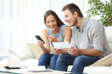 home expenses: Couple doing accounting on line with a phone bank app sitting on a couch in the living room at home
