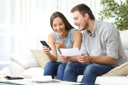 Pareja haciendo la contabilidad en línea con una aplicación de banco de teléfono que se sienta en un sofá en la sala de estar en casa