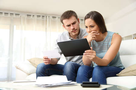 Worried couple checking bank account trouble online in a tablet sitting on a couch in the living room at home Фото со стока