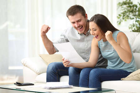 Excited couple reading a letter together sitting on a sofa in the living room at home
