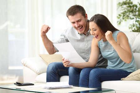 Opgewonden paar samen lezen van een brief op een bank in de woonkamer thuis