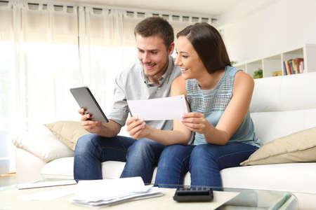 Gelukkige paar die bankrekening op lijn in een tablet zit op een bank in de woonkamer thuis Stockfoto