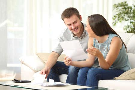 Gelukkig paar lezen e-mail en het controleren van de boekhouding op zoek elkaar zittend op een bank thuis Stockfoto - 65815550