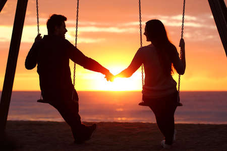 暖かさの背景に太陽とビーチで日の出を見て手を繋いでいるスイングの上に座ってカップルのシルエットの戻る光の肖像画 写真素材 - 65879360