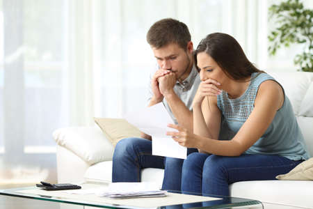 Worried couple reading an important notification in a letter sitting on a couch in the living room at home Фото со стока