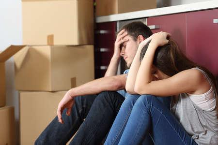 Angry uitgezet paar bezorgd verhuizing zittend op de vloer in de keuken