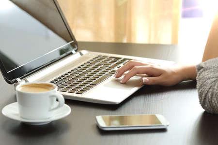 バックライトは背景でウィンドウを家のデスクトップに座ってノート パソコンでウェブサイトを閲覧して女性の手のクローズ アップ