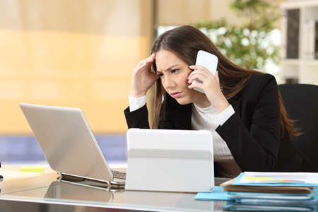 worried executive: Worried executive talking on the phone trying to solve problems with multiple devices sitting in a desktop at office Stock Photo