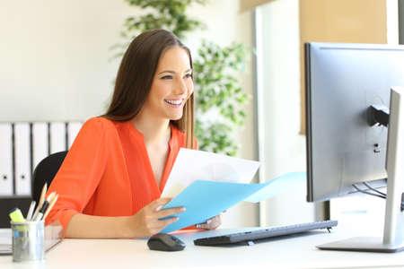 執務室の机に座っているコンピューターとドキュメントを比較する起業家やエグゼクティブの作業