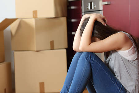 eviction: Sad evicted woman worried moving house sitting on the floor in the kitchen Stock Photo