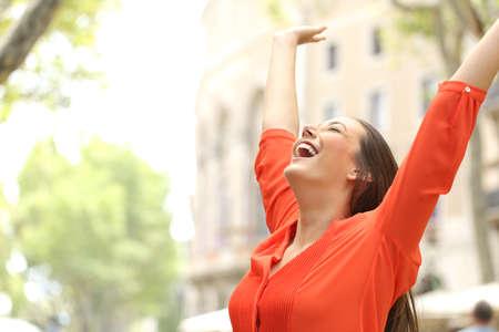 Emocionado mujer con blusa naranja levanta los brazos al aire libre en la calle con edificios en el fondo Foto de archivo
