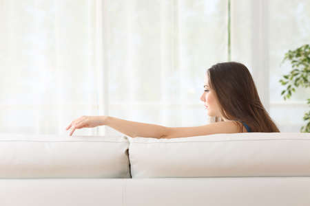 cheated: Sad woman sitting on a couch missing her lost husband touching the empty seat at home Stock Photo