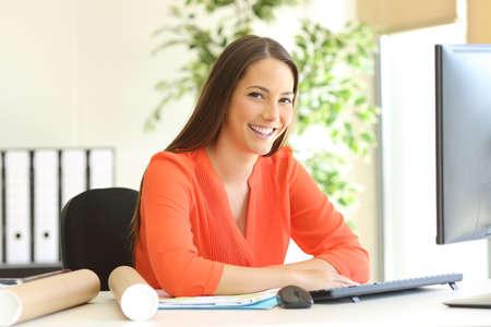Diseñador o arquitecto posando y mirando a usted sentado en un escritorio en la oficina con una ventana en el fondo